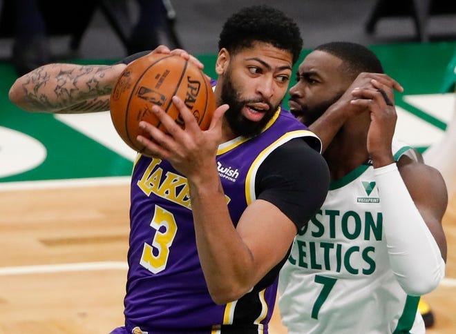 Athony Davis busca quitarse la marca en una jugada de Lakers.