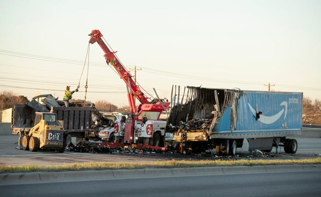 Debris is removed after a fatal accident on Texas 71 between East Riverside and Montopolis drives on Monday February 1, 2021.  One person was killed early in the crash involving an 18-wheeler and a vehicle that happened around 2:07 a.m., Austin-Travis County EMS medics said.