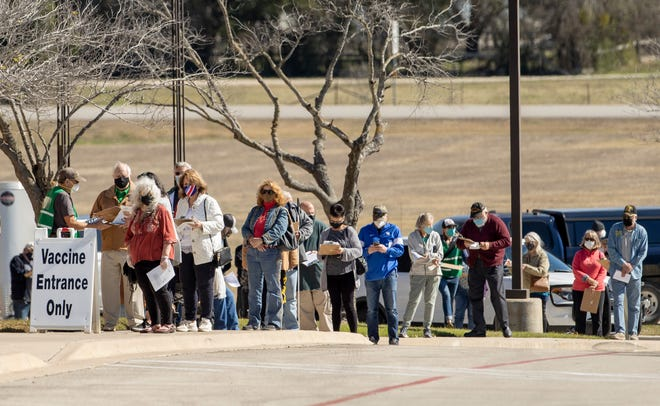 People wait in line for a COVID-19 vaccine at the Hays school district's Performing Arts Center in Kyle on Feb. 1. The district on Wednesday said a middle school student in Buda tested positive for the United Kingdom variant of the coronavirus.