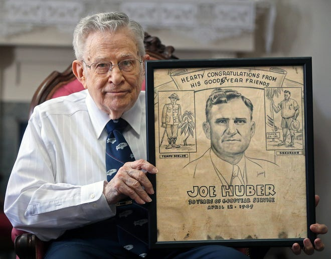 Joe Huber Jr., 86, of Cuyahoga Falls, shows a drawing of his father that was given to him in 1949 after 30 years of service at Goodyear. The family lived on a rubber plantation in the Philippines and spent time in prison camps during World War II.