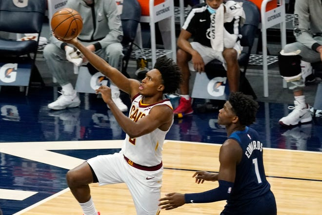 Cavaliers' Collin Sexton (2) lays up as Minnesota Timberwolves' Anthony Edwards (1) looks on in the first half of an NBA basketball game Sunday, Jan. 31, 2021, in Minneapolis. [Jim Mone/Associated Press]