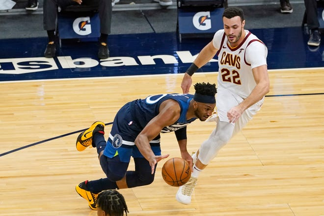 Minnesota Timberwolves' Josh Okogie, left, drives around Cavaliers' Larry Nance Jr. (22) in the first half of an NBA basketball game Sunday, Jan. 31, 2021, in Minneapolis. [Jim Mone/Associated Press]