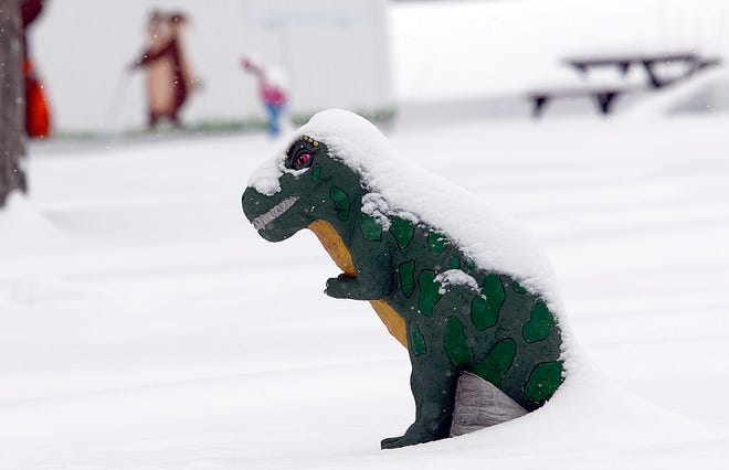 The dinosaur statue at a miniature golf course at  is snow covered from the snow. [TOM E. PUSKAR/TIMES-GAZETTE.COM]