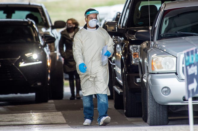 Medical personnel walk between cars as they collect samples from motorists for COVID-19 testing at the Augusta University Health System testing site in Augusta, Ga., Monday afternoon February 1, 2021.