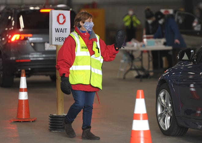 Community Emergency Response Team volunteer Jane Sullivan, of Brewster, helps to direct drivers into the Orleans Department of Public Works garage area during a regional COVID-19 clinic last week. Volunteers with the Cape Cod Medical Reserve Corps were also on site to help with the clinic.