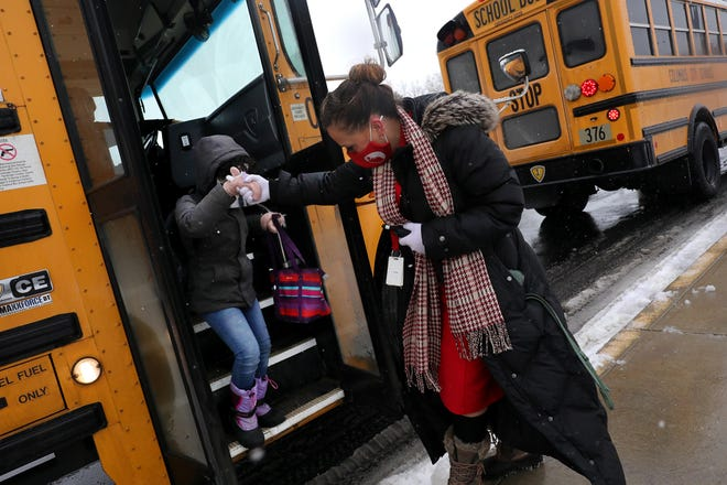 Ohio Avenue, Innis and and Easthaven elementary schools shifted back to virtual instruction Monday due to lack of substitute teachers available to cover teachers out sick. In this Feb. 1 file photo, Principal Emma Corbin helps a student get off the bus after arriving at Ecole Kenwood French Immersion Elementary School.