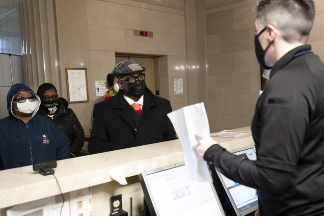 The Rev. Jefferey P. Kee, center, of New Faith Baptist Church of Christ, along with Paisha Thomas, left, Adrienne Hood second from left, and the Rev. Susan K. Smith, background, deliver a petition for Mayor Andrew J. Ginther demanding the termination of former Columbus Police Chief Thomas Quinlan on Feb. 1.