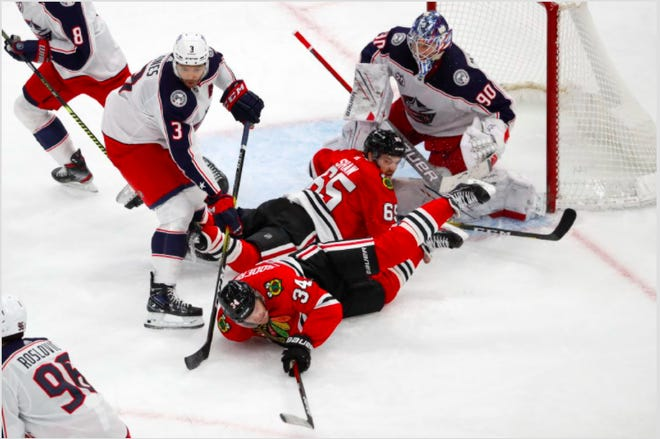 Chicago Blackhawks center Carl Soderberg (34) and teammate Andrew Shaw (65) collide while going for the puck as the Blue Jackets' Seth Jones (3) and goaltender Elvis Merzlikins (90) defend during the third period Sunday night in Chicago. (AP Photo/Jeff Haynes)