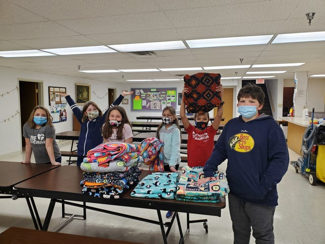 McKinna Amiot, Lily Olmstead, Blake Brockpahler, Ruby Larson, Teagan Stueber, and Nolan Johnson stand by a small portion of the blankets the students helped to finish.