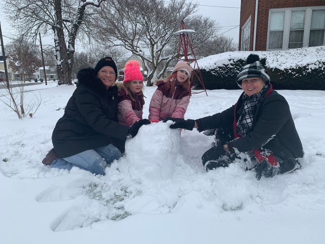 Kathy Craft, sisters Annabell Moran, 6, and Annika Moran, 10, and Karen Jenkins work on building a snowman outside Jenkins' home in Creston on Monday.