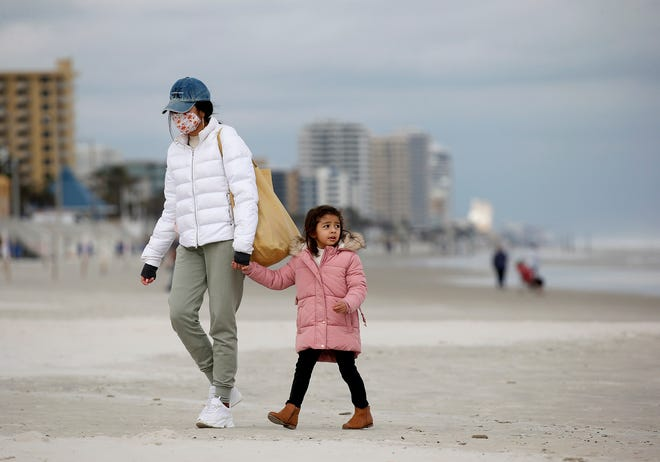 A woman and child brave the chilly winds on Daytona Beach on Monday, Feb 1, 2021. Temps were expected to drop into the mid-30s Tuesday and Wednesday morning, with wind chills making it feel like 29 degrees.
