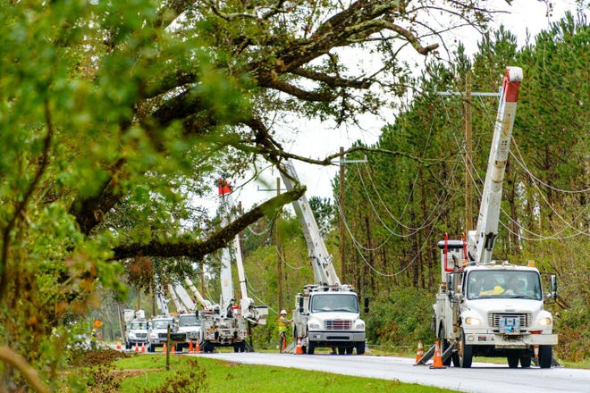 Crews work together to fix power lines.