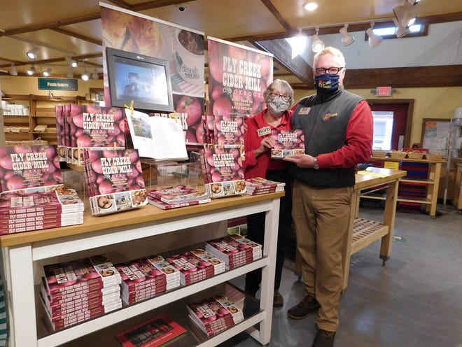 Fly Creek Cider Mill and Orchard owner Bill Michaels and his mother, Barbara, stand beside a display of Fly Creek Cider Mill cookbooks. The popular attraction closed its doors at the end of the day Sunday.