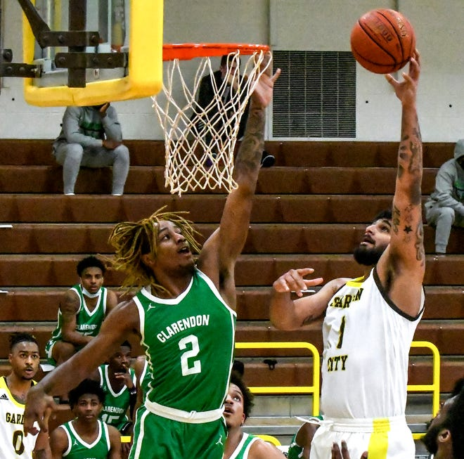 Garden City Community College's Jasman Sangha, right, goes up for a basket over Clarendon's Zarique Nutter Saturday at Perryman Athletic Complex.