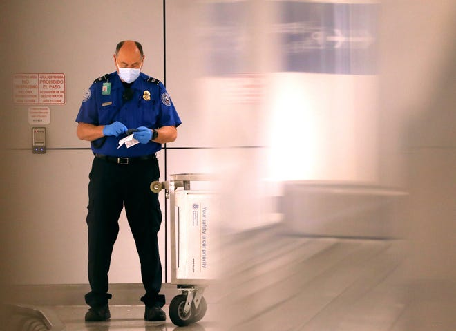 A TSA agent checks his cell phone while wearing a mask and gloves at Sky Harbor Airport in Phoenix, Ariz. on March 12, 2020. The U.S. Department of Homeland Security on Sunday gave enforcement authority to TSA employees against anyone trying to fly without a mask.