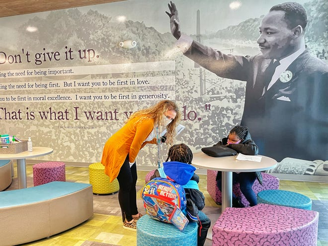 FILE PHOTO: Dr. Martin Luther King Jr. Elementary School principal Val Hawkins, left, speaks with kindergartners Messiah Jenkins, center, and Royal Payne, both 5, in the front foyer of the school on the first day on in-person learning in District 205 on Feb. 1, 2021. On Thursday, students at King learned they will go back to remote learning Friday due to a COVID-19 outbreak.