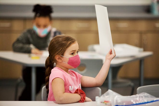 Dr. Martin Luther King Jr. Elementary School student Makenzie Wells holds up her paper during Angela Harshbarger's first grade class on the first day of in-person learning in District 205 on Monday, Feb 1, 2021.