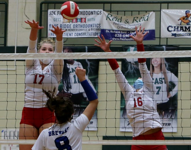 Hendersonville's Emily Beeker (17) and Chloe Conroy go up for a block against Brevard at a match earlier this season at East Henderson.
