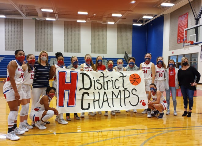 The Heritage girls basketball team holds a banner celebrating another district championship on Saturday after the Jaguars beat Venus, 69-36.