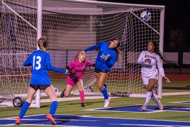 Midlothian's Neriah Crouch (21) heads the ball out of danger in front of the goal as keeper Landry Combs (0) and teammate Nevaeh Higgins (13) look on during Friday night's District 14-5A match against Red Oak at the Roesler Athletic Complex. The Lady Panthers won, 3-2.
