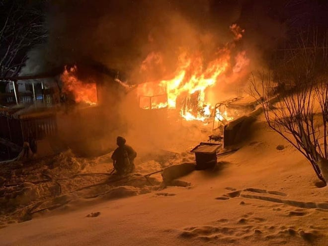Firefighters battle the elements as well as the fire the Roosevelt Street home of Leo and Debra Nesmith of Westernport.