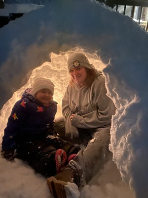 Alahna Redman, 3, is joined by Rachel Ravenscroft in her igloo at the Stoney Run Road home of her dad, Josh Redman. The family spent their snow-filled Sunday building the igloo and having fun together. Snow was expected to continue falling throughout the day Monday until approximately midnight.