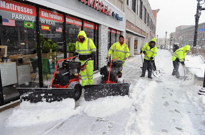 Lucas Aranda, left and Mavricio Nunes lead a  snow clearing crew on Concord Street in downtown Framingham, Feb 1, 2021.