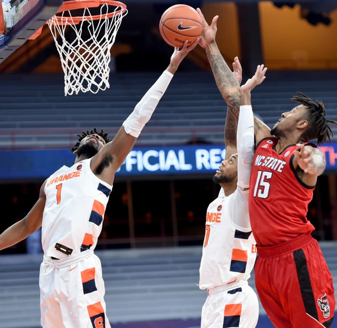 Syracuse forwards Quincy Guerrier (1), and Alan Griffin (0) battle North Carolina State forward Manny Bates (15) for a rebound Sunday at the Carrier Dome.