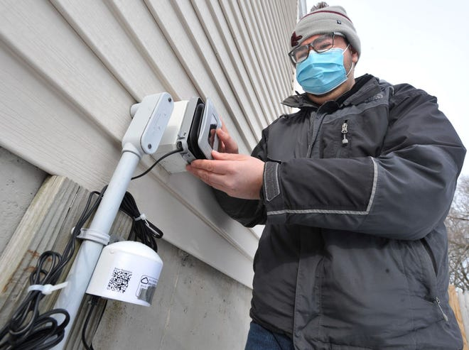 Robert Kearns of the Fore River Residents Against the Compressor Station checks the newly installed air monitoring station outside of a Quincy Point home that will detect any emissions from the Fore River natural gas compressor station in North Weymouth, Friday, Jan. 29, 2021.