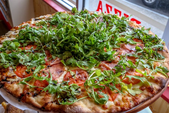 Arugula prosciutto pizza pairs cured meat with greens.