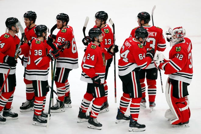 Former Rockford IceHogs goaltender Kevin Lankinen (32) celebrates with his Chicago Blackhawks teammates after defeating the Columbus Blue Jackets on Sunday, Jan. 31, 2021, in Chicago.