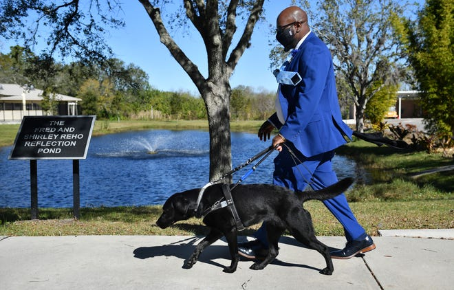 Gary Ernneus practices commands with his new seeing-eye dog, Tahoe, on the campus of Southeastern Guide Dogs in Palmetto.
