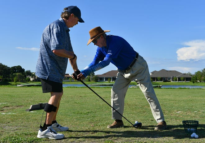 Doug Erb, a longtime Sarasota golf pro, helps stroke-victim Tom Boyle with his grip on the driving range at The Palms Golf Club at Forest Lakes in Sarasota in 2019. Erb died last week at the age of 76.