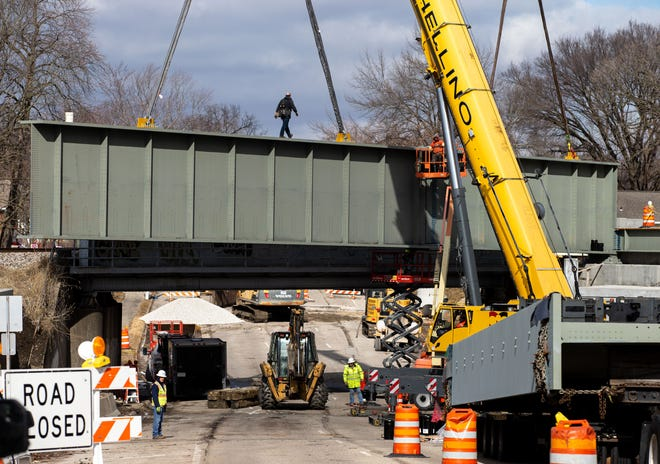 A worker traverses a section of the new double-track railroad bridge as it is held in place by two cranes during construction on the Fifth Street overpass in Springfield, Ill., Monday, February 1, 2021. The stretch of Fifth Street from Broad Place to Iles Avenue is set to reopen Monday afternoon.