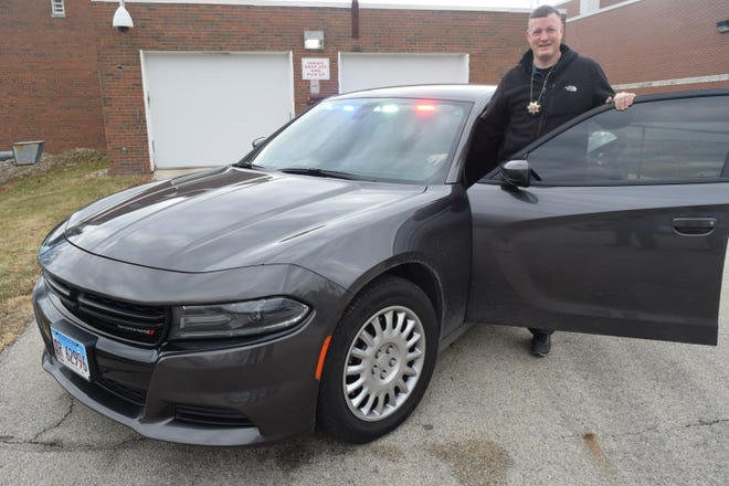 Henry County Sheriff's detective Sgt. Josh Verscheure last year shows off the new investigator's car, one of six Dodge Chargers the sheriff's department purchased with the proceeds of the public safety sales tax.
