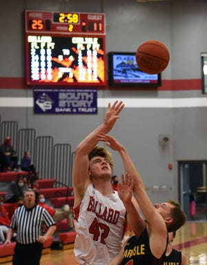 Ballard's Jacob Ihle flips up a shot over Carlisle's Tyson Guard on a drive during the second quarter of the Bombers' 57-34 victory over the Wildcats Saturday at Huxley.