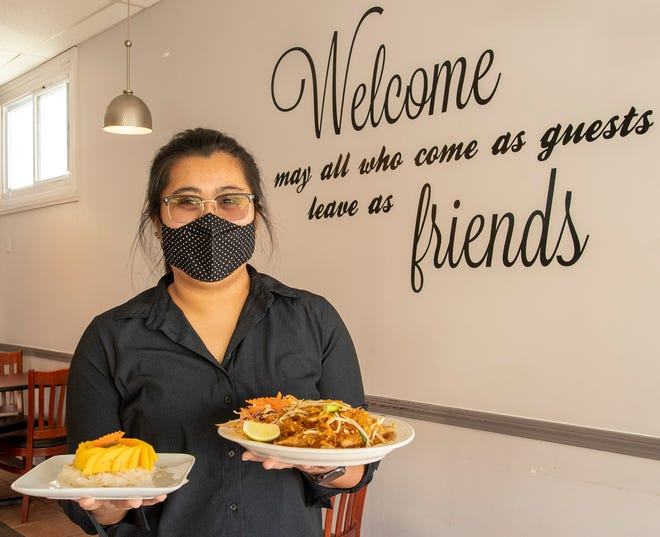 Thai Corner owner Revadee (Ray) Chueawong holds her mango with sweet rice, left, and Pad Thai Woonsen  at the restaurant.