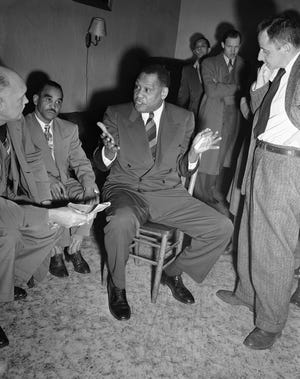 "Baritone Paul Robeson gestures at a conference in Marine Cooks and Stewards headquarters in Seattle, Washington, Feb. 1, 1952. Robeson was refused permission to cross into Canada the day before where he was to address a convention of the Mine, Mill and Smelter Workers' union. Robeson said the State Department was depriving him of the ""basic power of freedom of speech"" by refusing to let him attend the meeting."