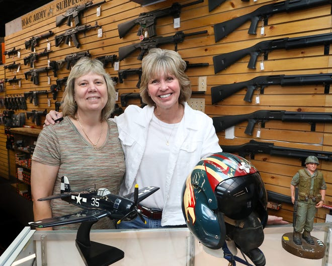 Olivia Cason, left, and Suzanne Miller, who have owned M&C Army Surplus Store on Northwest 13th Street for more than 35 years, pose in the Gainesville store last week. The two plan to close the military surplus store at the end of the month.