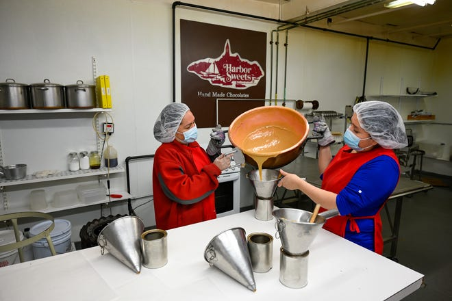 Employees pour a fresh batch of caramel into funnels at Harbor Sweets in Salem as they prepare for Valentine's Day on Monday, Feb. 1, 2021.
