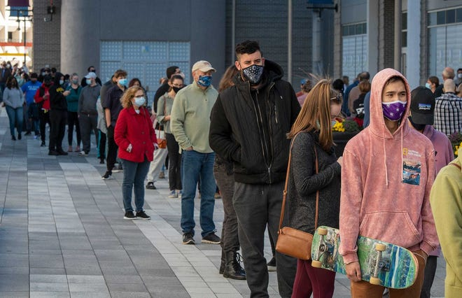 People line up at a free COVID-19 testing site at Mercantile Center courtyard in downtown Worcester in December. Students at the College of the Holy Cross have been chronicling the history of the pandemic in real time and its impact on the community.