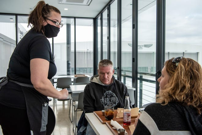 Server Ashley Kleinfelt brings appetizers to Aaron and Rhonda Wiersma at WACO Kitchen on Monday, Feb. 1, 2021 in Battle Creek, Mich. Indoor dining is now permitted in Michigan with restrictions, such as operating at 25% capacity and following a 10 p.m. curfew.
