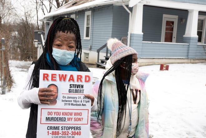 Lawanda Gilbert visits the house where her son, Steven Gilbert, was murdered seven years ago, with Steven Gilbert's great-niece Zyaire Lawson, 10, in East Price Hill on Monday, Feb. 1, 2021. Steven was murdered on January 31, 2014.ÊEach year Gilbert stands in front of the house where her son lived with his wife and children at the time of his death.