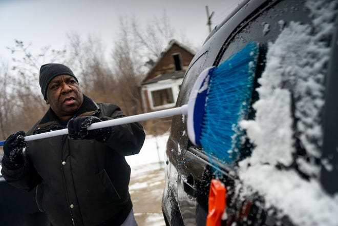"""Jimmy Parker cleans snow off his car at his home on Sunday, Jan. 31, 2021, in Detroit. """"I like the fresh air. It's quiet. No one's around,"""" he said."""