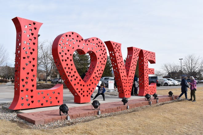 People gather around the love lock sculpture outside of the Loveland Visitors Center Monday, Feb. 1.
