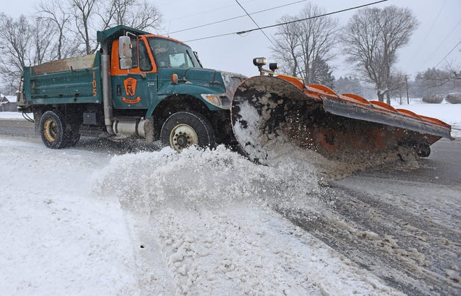 A Richland County snow plow driver clears snow at the intersection of Lexington-Springmill Road and Alta Road on Monday morning.