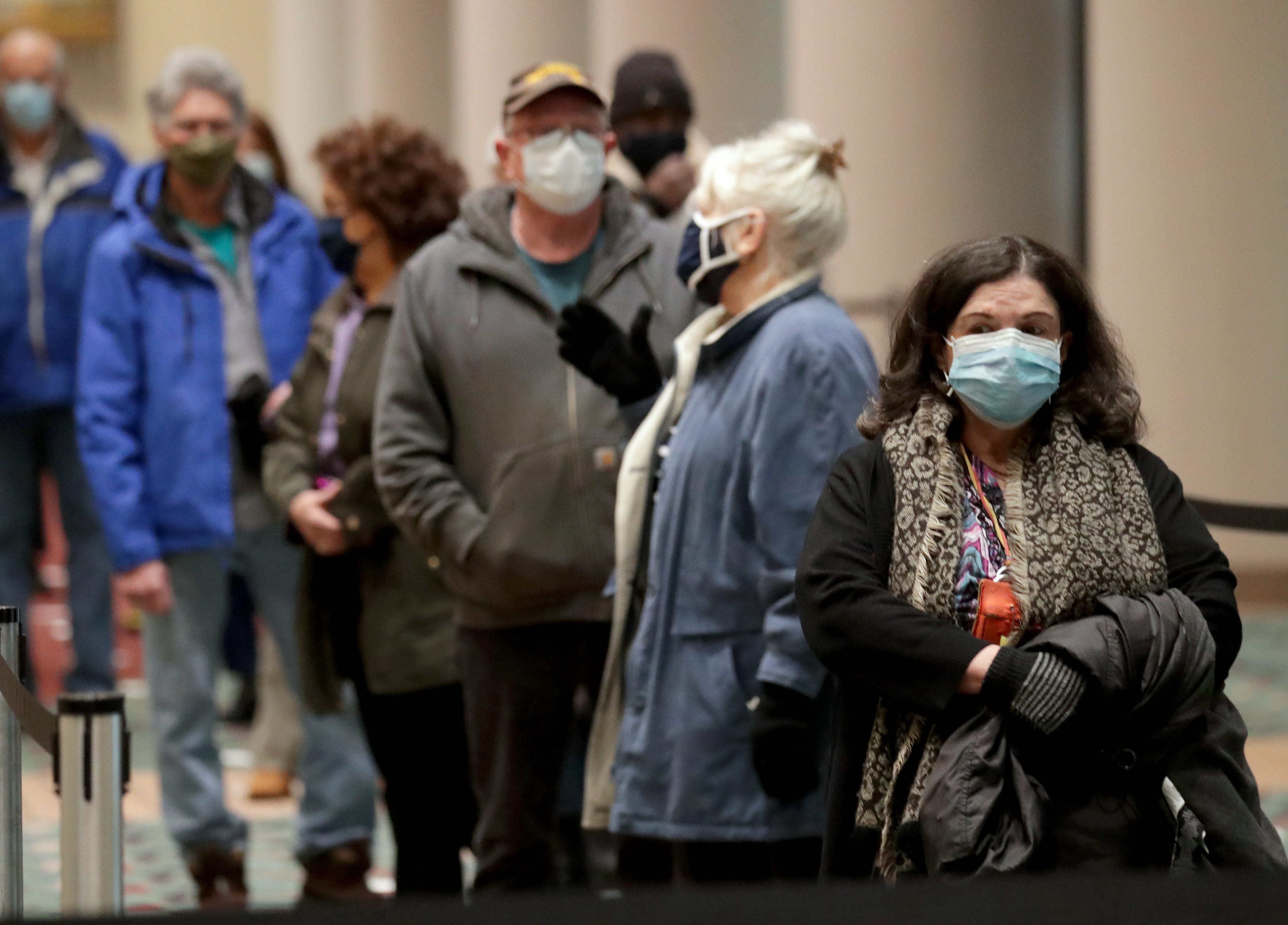 People wait to get the COVID-19 vaccination at the Wisconsin Center in Milwaukee on Monday, Feb. 1, 2021.
