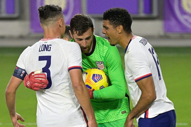 United States goalkeeper Matt Turner, center, is congratulated by defenders Aaron Long (3) and Miles Robinson (12) after stopping a penalty kick by Trinidad and Tobago defender Alvin Jones during the second half of an international friendly soccer match, Sunday, Jan. 31, 2021, in Orlando, Fla. (AP Photo/Phelan M. Ebenhack)