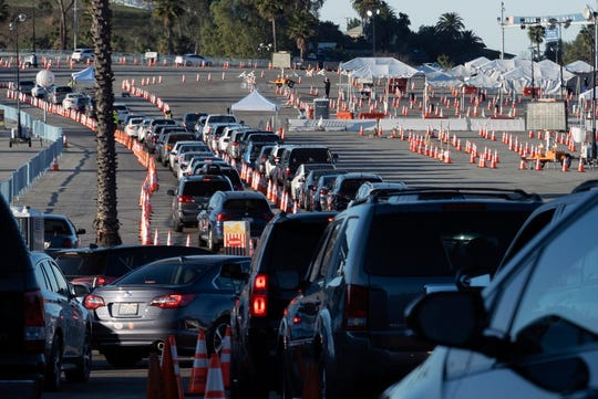 Los Angeles residents wait in line in their cars to receive a covid-19 vaccine at Dodger Stadium, on Jan. 26, 2021, in Los Angeles. California is revamping its vaccine delivery system to give the state more control over who gets the shots following intense criticism of a slow and scattered rollout by counties.