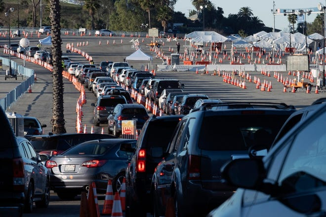 Los Angeles residents wait in line in their cars to receive COVID-19 vaccines at Dodger Stadium on Jan. 26 in Los Angeles.